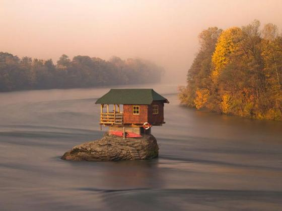 tiny house in the middle of a lake, tiny house, beautiful little cabin, sun setting