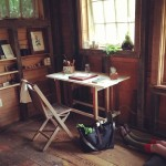 peg and awl, beautiful desk in cozy cabin, natural setting, writing desk, legs in stockings, natural light hitting paper, simplistic living, a writers dream